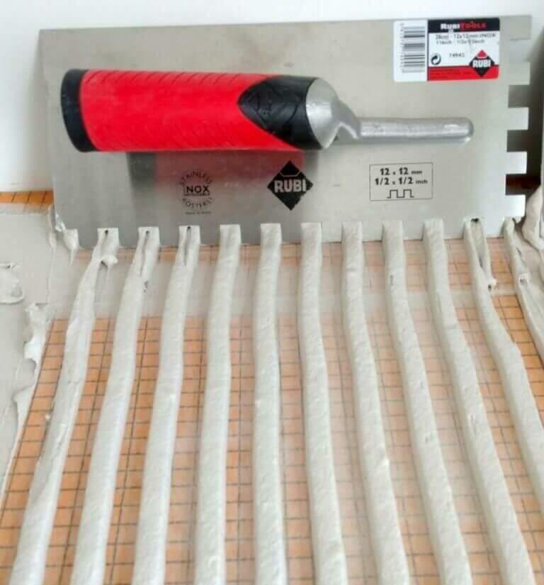 un peigne à encoche en U de 10 mm laisse un lit d'adhésif de 3 mm