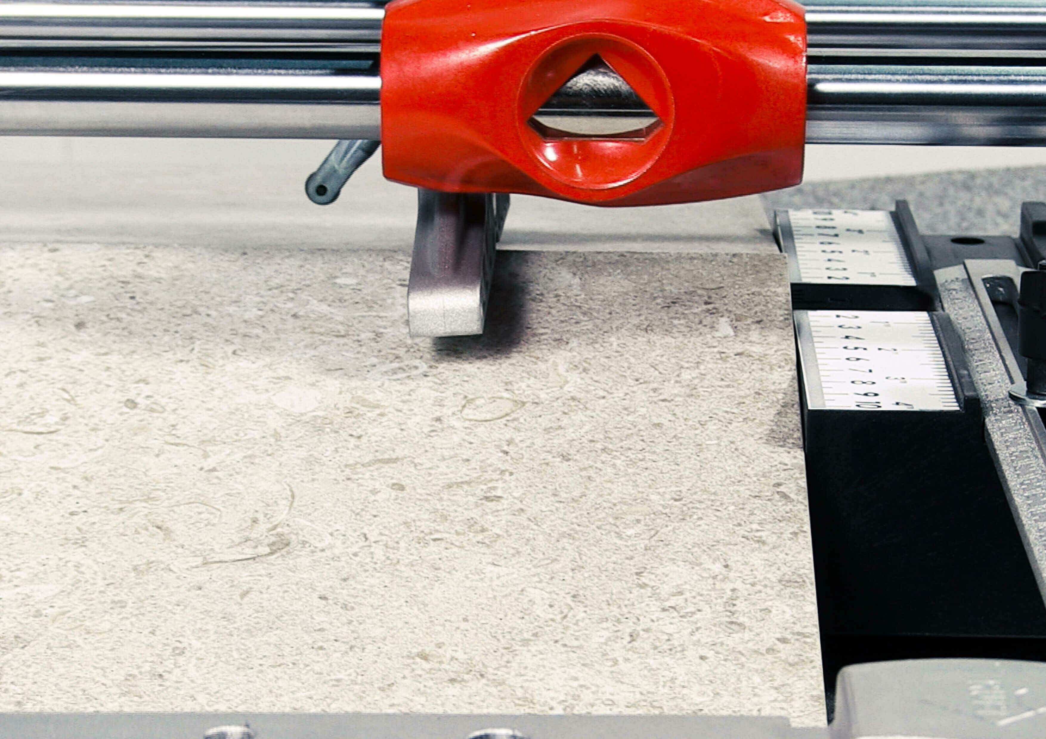 Close-up van een breekvleugel van een tegelsnijder. De tegel die op de tegelsnijplank ligt, is doormidden gebroken.