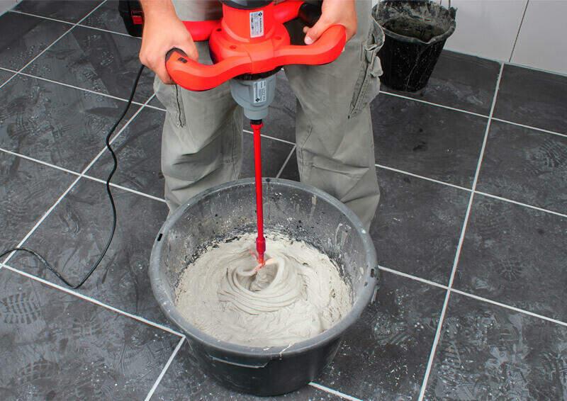 Professional mixt staand de lijm in een kunststof emmer met de RUBIMIX elektrische mixer.