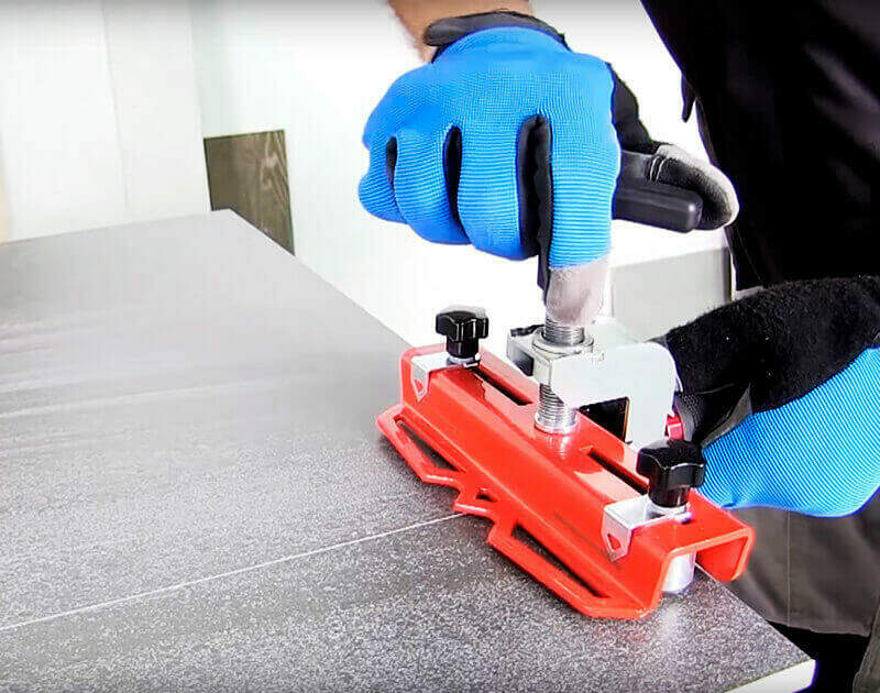Een tegel wordt gebroken met de RUBI SLIM breker: een breeksysteem voor grootformaat tegels met een dikte tot 15 mm.