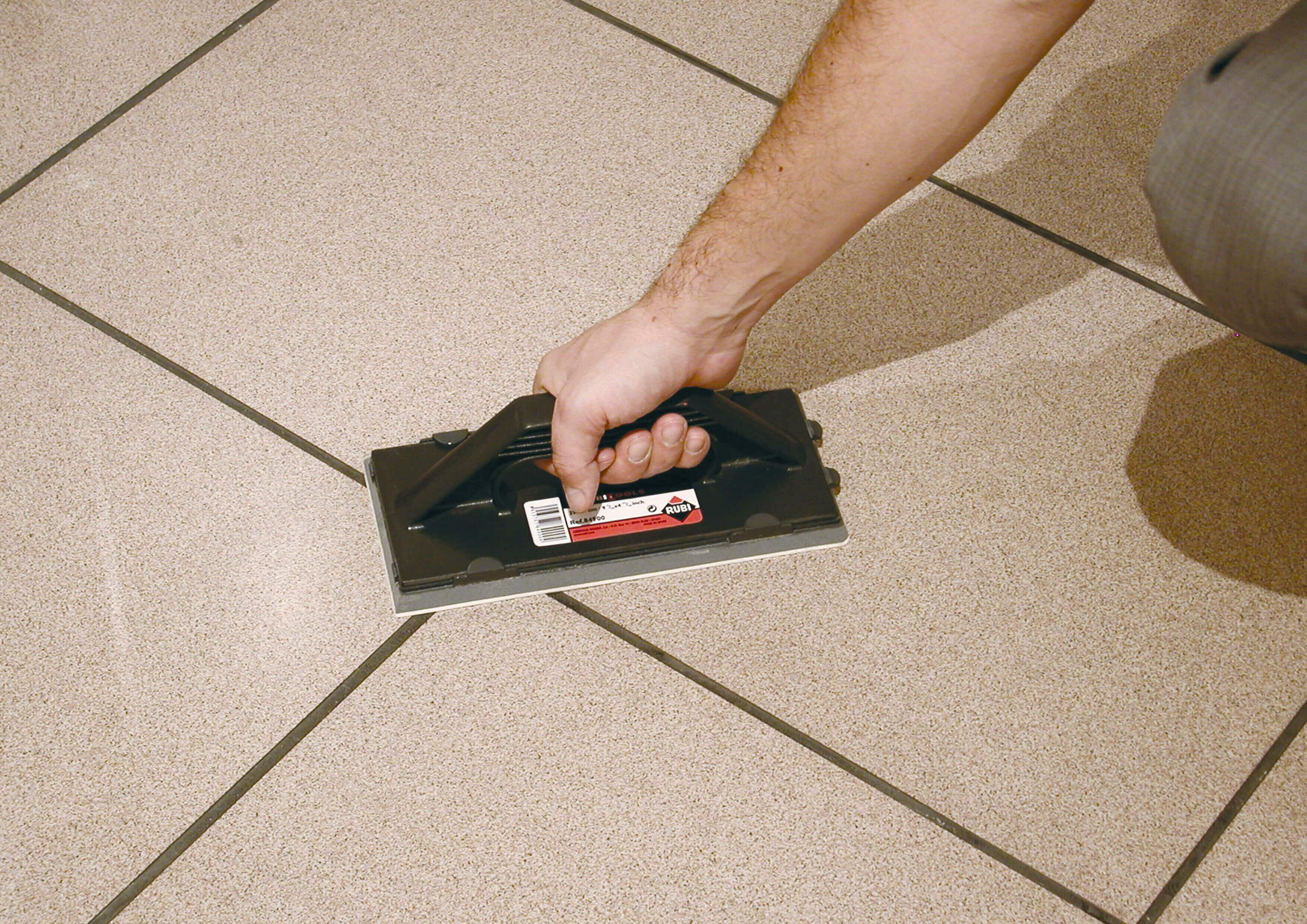 Spaan voor tegels voegen met een ´ruitenwissereffect´ om minder voegsel op de tegel achter te laten.
