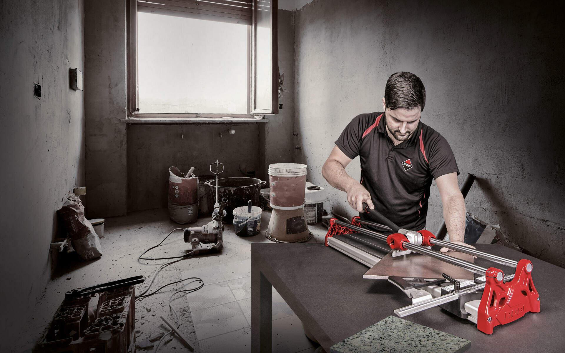 Een tegelzetter snijdt een tegel diagonaal. Tegelsnijders staan bovenaan het rijtje van onmisbare gereedschappen.
