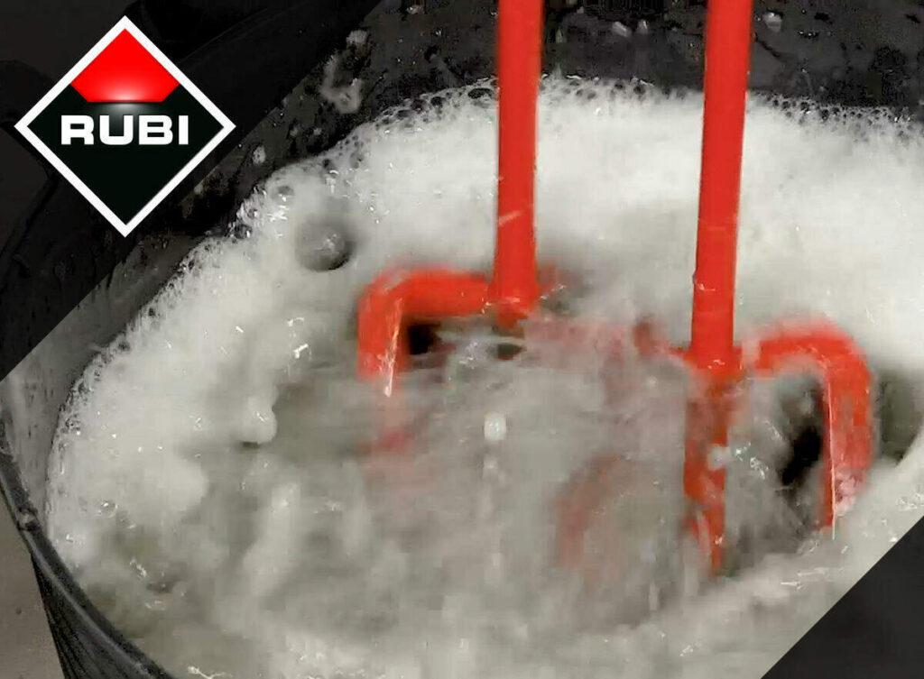Reinig de mengstaaf van een mixer in een emmer met water en zand.