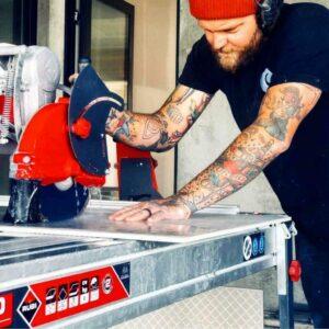 Een tegelzetter zaagt met een zaagmachine regelmatig buiten.