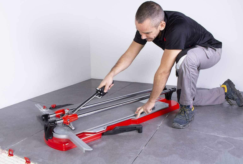 Een tegelzetter snijdt op de grond een tegel met een TX-MAX tegelsnijder.