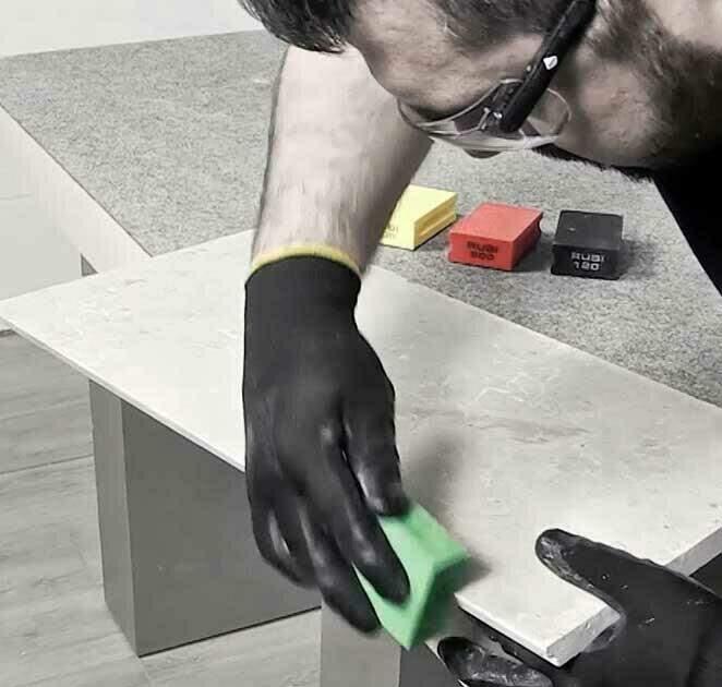 Met een RUBI polijstpad worden de scherpe randen van een tegel bewerkt - tegels zetten.