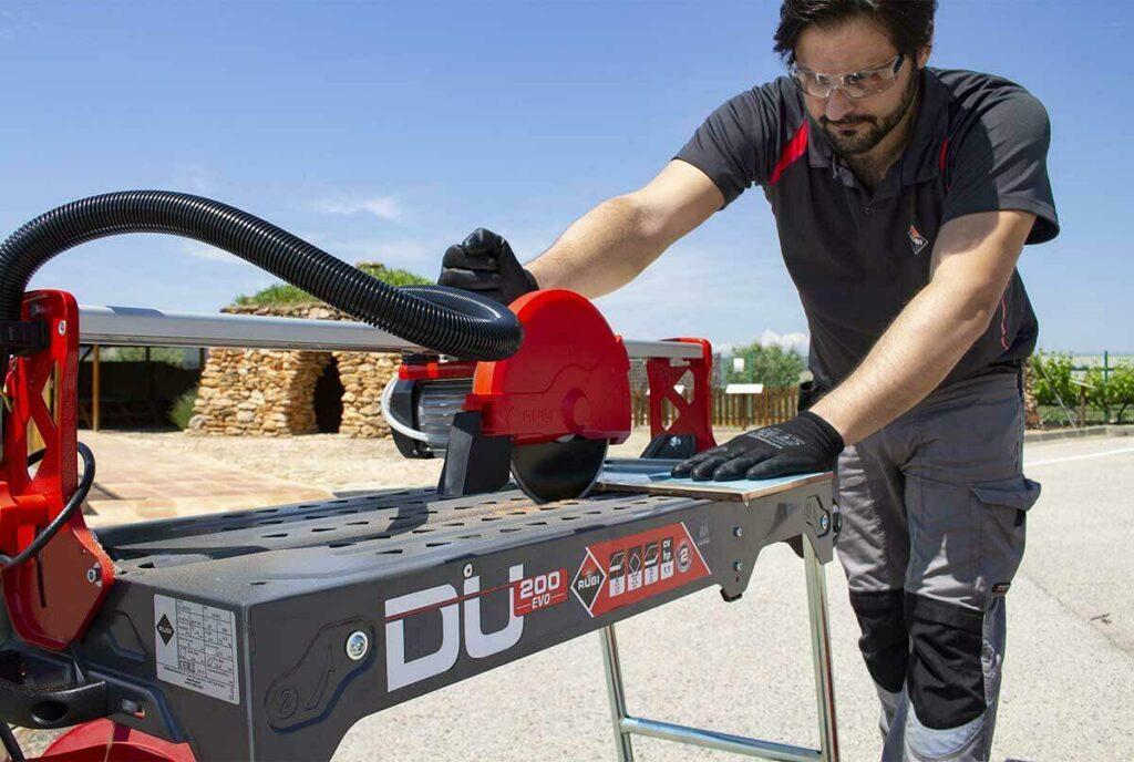 De motor van de RUBI DU-200 EVO zaagmachine wordt door een gebruiker bewogen over de rail.