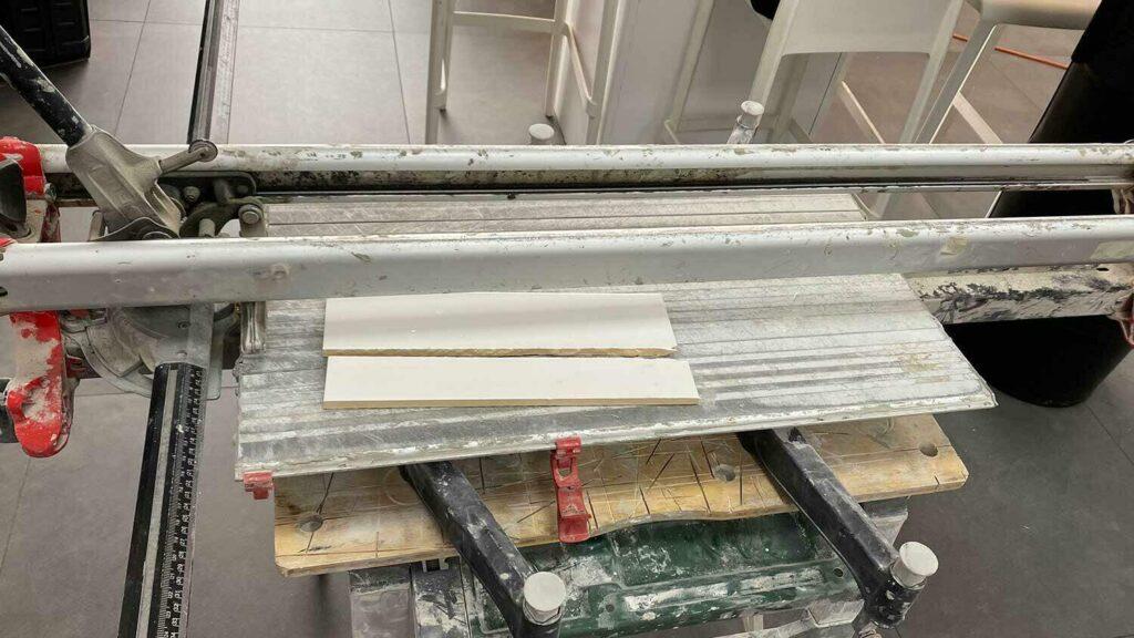 Een RUBI TZ tegelsnijder met keramische resten op de plank.
