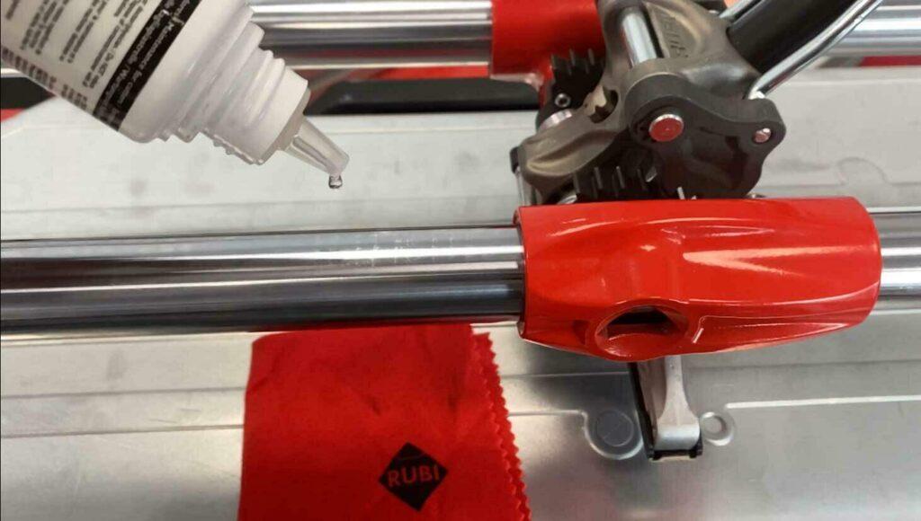 De geleidestangen van een RUBI TX-MAX tegelsnijder krijgen een beetje olie om deze soepeler te laten lopen.