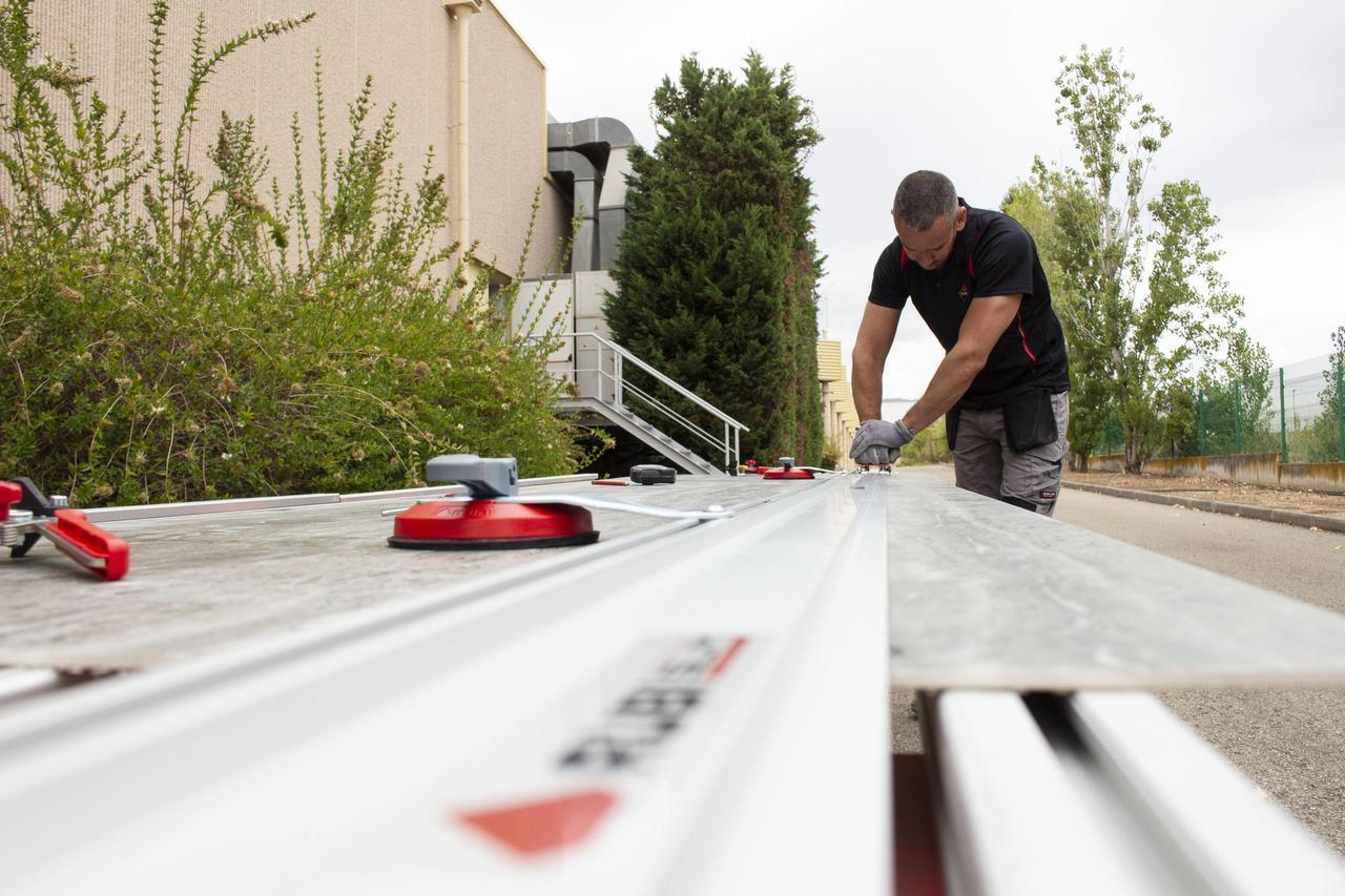 Een keramische plaat wordt in de buitenlucht op een grote werktafel gesneden met de SLIM CUTTER PLUS handsnijder van RUBI.